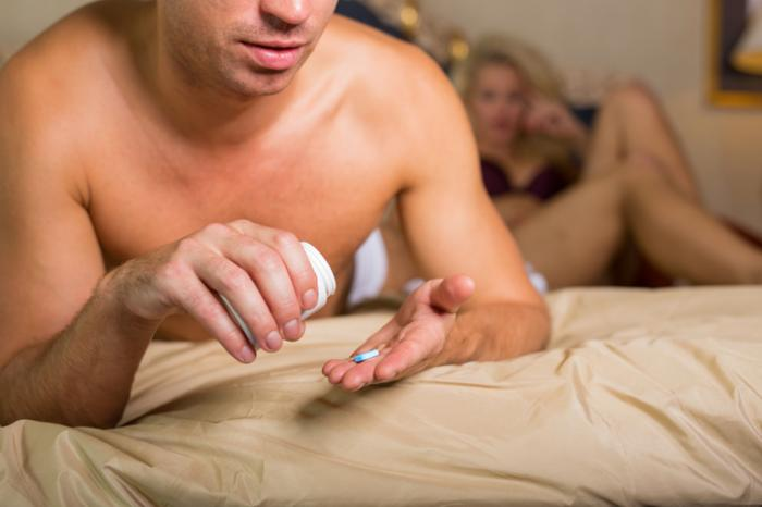 a man is taking a pill while in bed - Diabetes en erectiestoornissen: wat is de connectie?