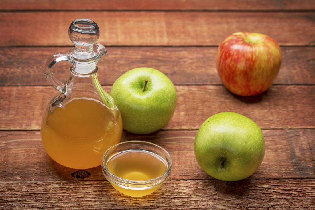 apple cider vinegar for detox in glass jar and bowl next to green and red apples n wooden table - Wat is de appelcider-azijn detox?