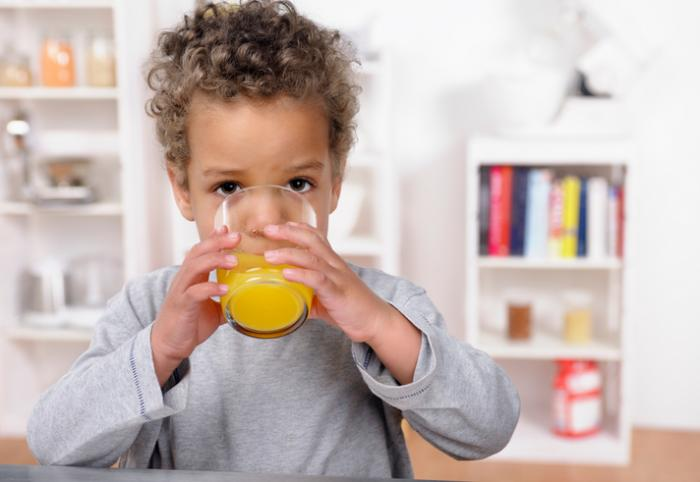 toddler drinking a glass of fruit juice - Wat is vitamine C? 34 gezonde eigenschappen van vitamine C